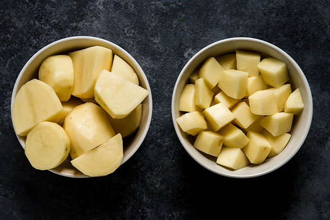 overhead photo of two bowls on a black background, one filled with large potato pieces and the other filled with small potato pieces