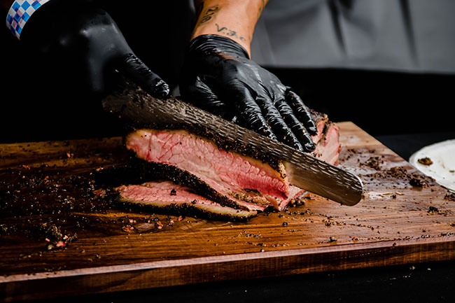 man's hands wearing black gloves slicing brisket on a wooden cutting board