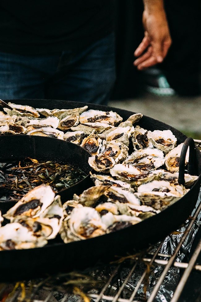 oysters in a black cast iron pan being smoked over a large fire
