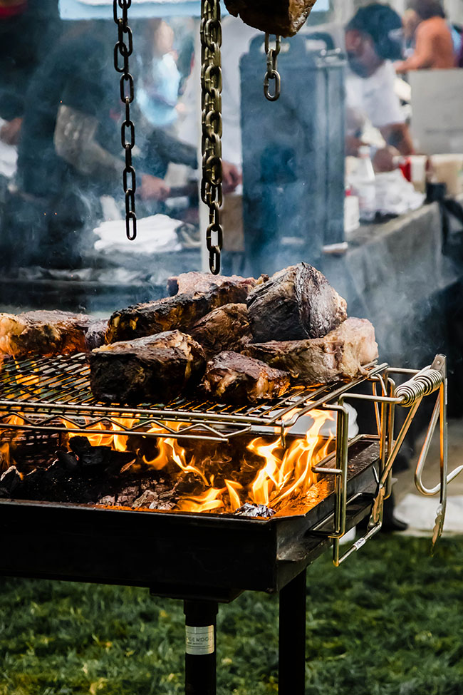meat smoking on a large grill over an open flame
