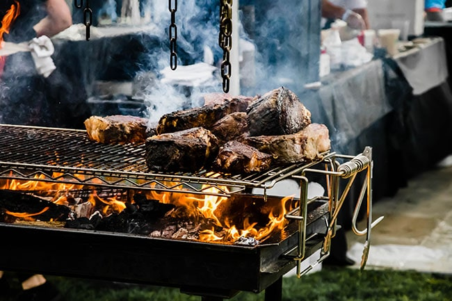Slabs of meat cooking on a grate over an open flame