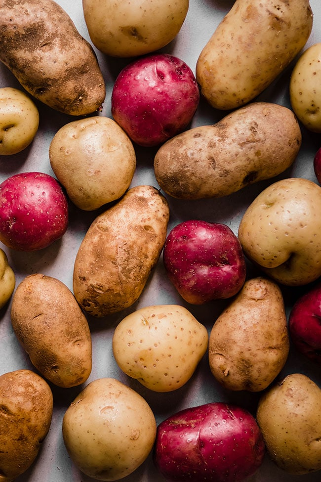 Overhead photo of different colored potatoes on a white background