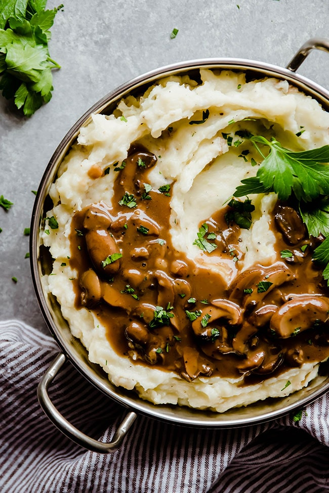 Overhead photo of mashed potatoes topped with mushroom gravy in a silver serving dish on a grey table