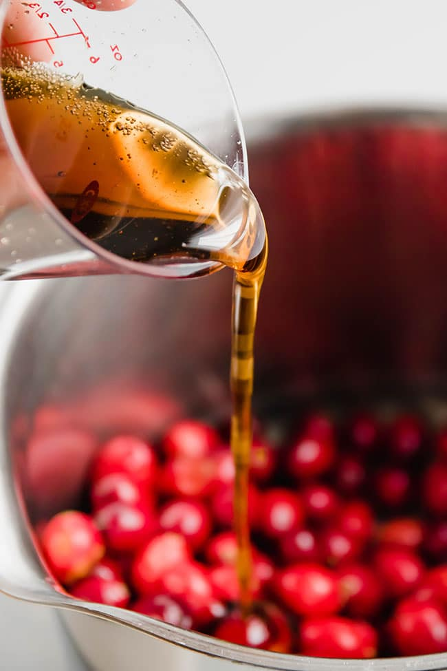maple syrup being poured into a pot of fresh cranberries