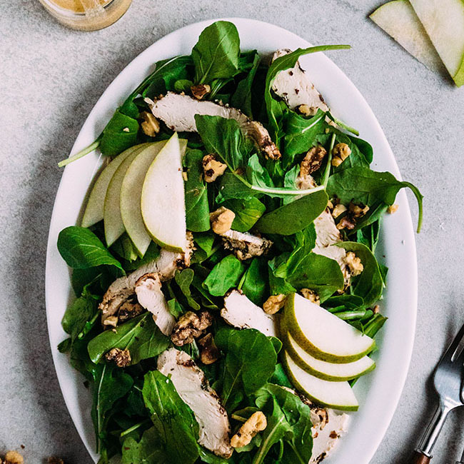 overhead photo of arugula salad on a white plate with sliced pears and walnuts