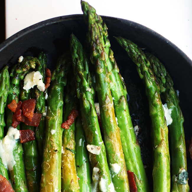 asparagus with bacon and blue cheese in a cast iron skillet