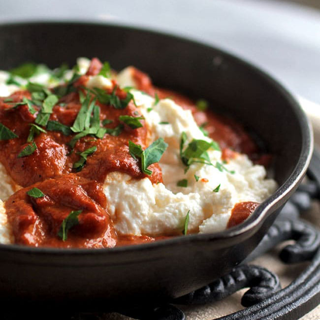 baked ricotta with roasted red pepper sauce in a cast iron skillet