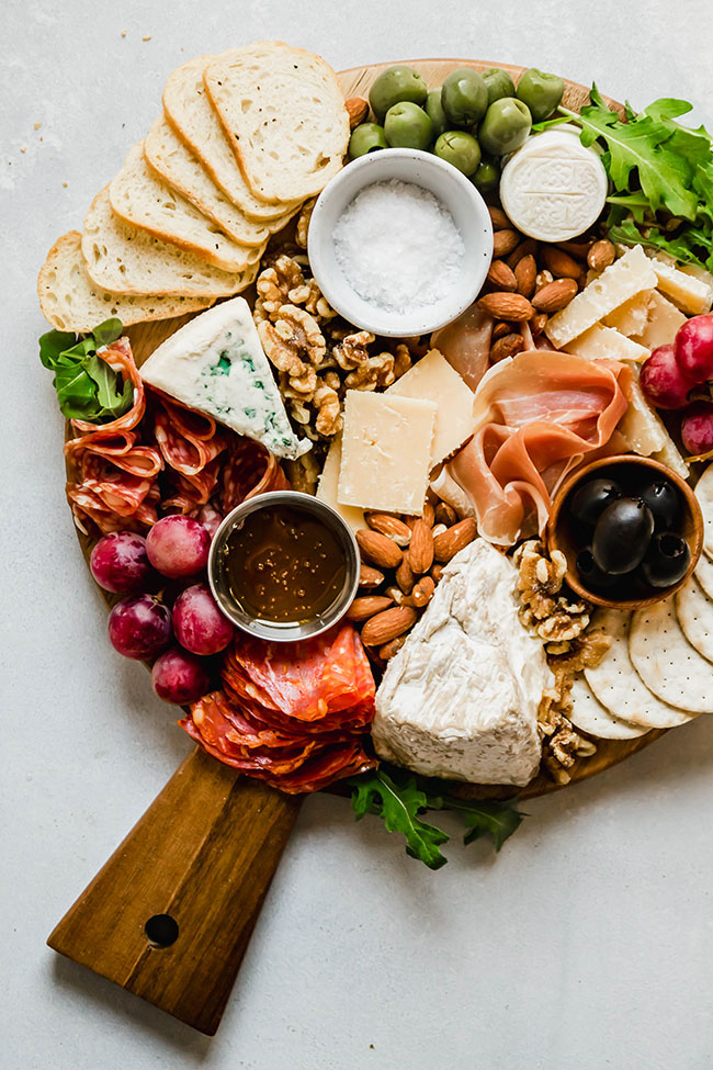 overhead photo of cheese and charcuterie on a wooden cutting board on a white table