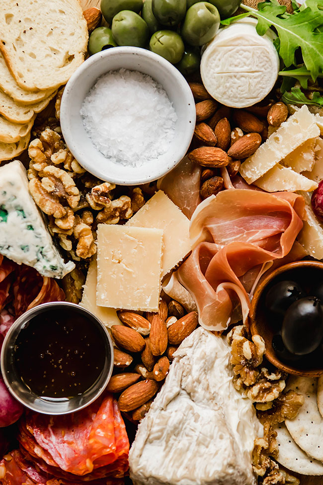 overhead photo of a cheese plate filled with nuts, cheeses, charcuterie, and olives