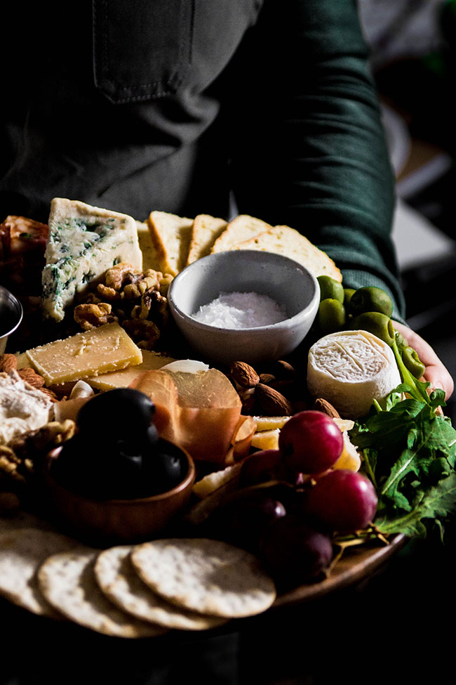woman holding a cheese board with goat cheese, grapes, black olives, and blue cheese