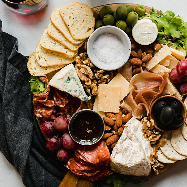 overhead photo of cheese plate on a wooden board