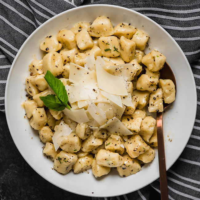 overhead photo of gnocchi topped with parmesan cheese in a shallow white bowl on top of a blue striped towel