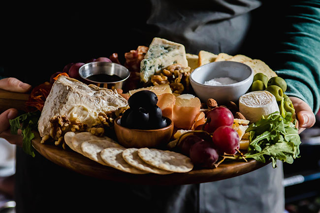 woman in a grey apron holding a cheese plate with crackers, arugula, brie, and black olives