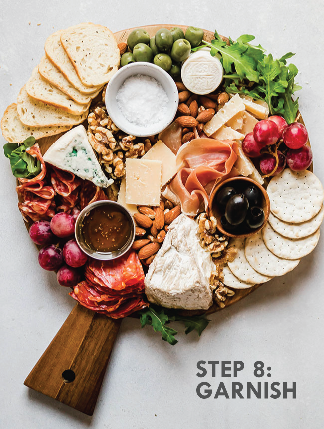 "overhead photo of cheese plate on a wooden cutting board on a white background with text overlay that reads ""step 8: garnish)"