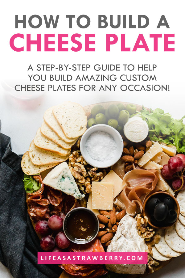 "overhead photo of a cheese and charcuterie platter with text overlay that reads ""how to build a cheese plate"" in grey and pink text"