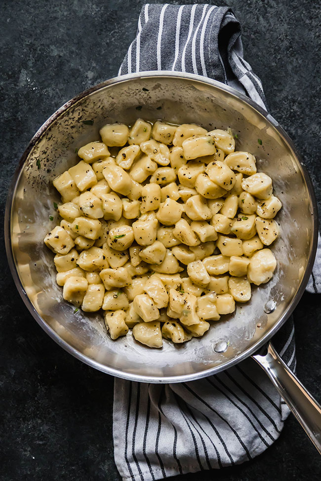 overhead photo of cooked gnocchi in a silver skillet sitting on a black countertop