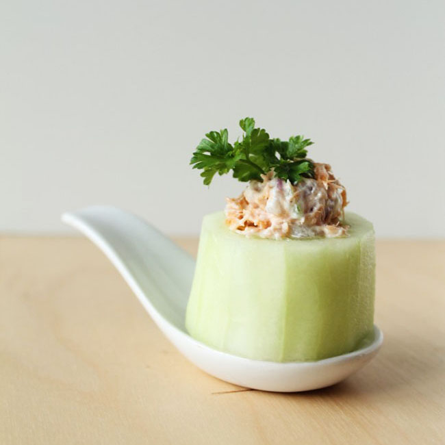 smoked salmon dip in a cucumber cup on a white spoon