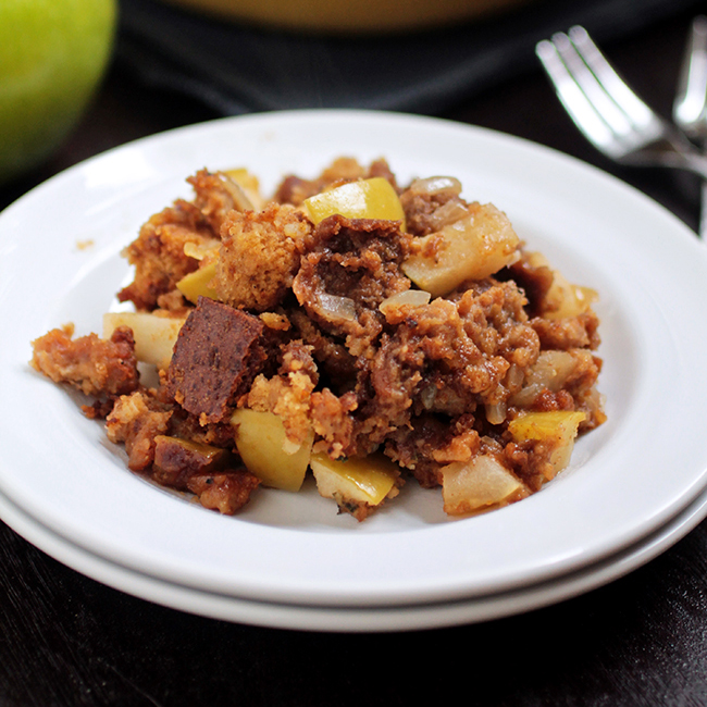 stuffing on a white plate next to a fork on a black background