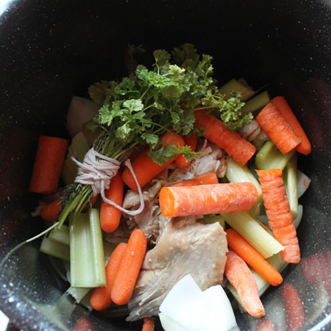 overhead photo of turkey stock ingredients in a large black pot