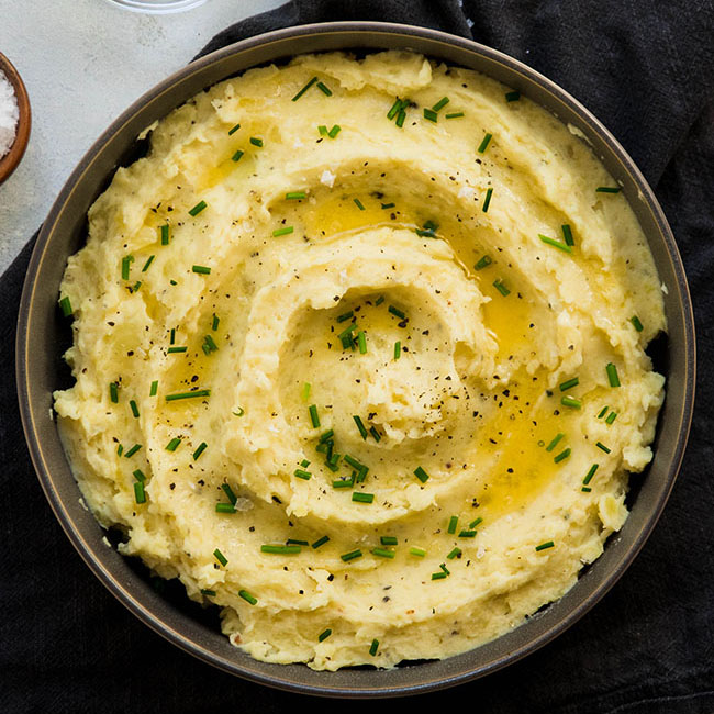 overhead photo of mashed potatoes topped with melted butter and chives in a grey bowl on a white table