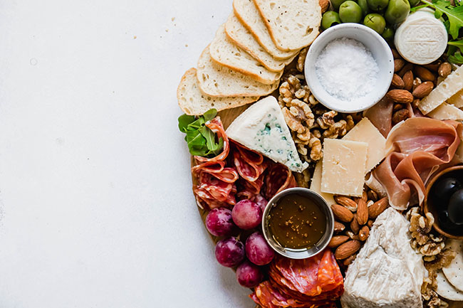 overhead photo of an off-center cheese board on a white background