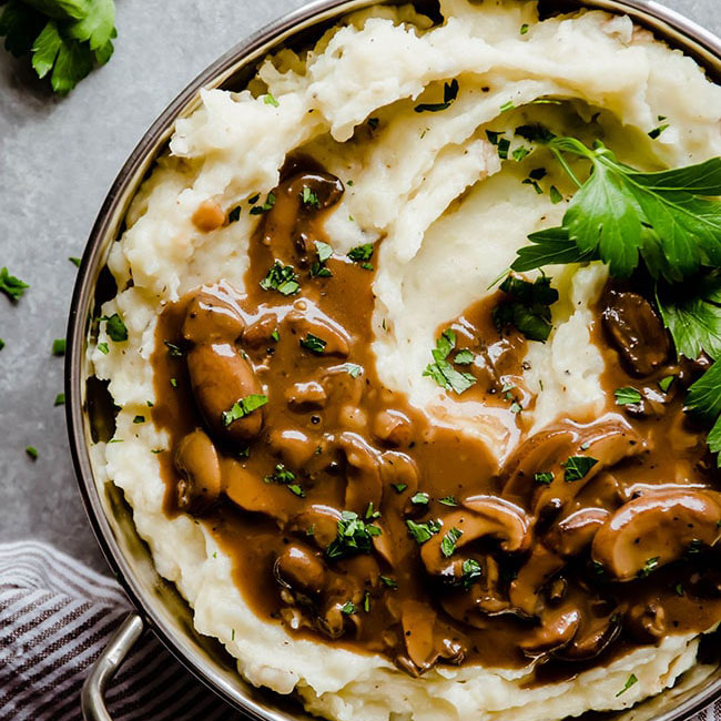 Overhead photo of mashed potatoes in a silver bowl with mushroom gravy and parsley on top
