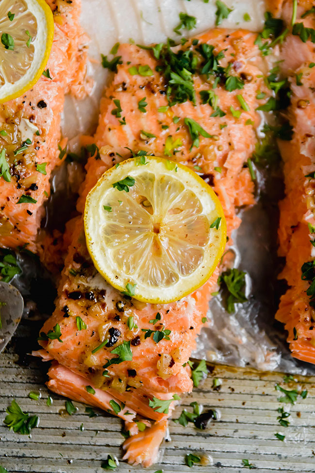 Baked steelhead trout on a metal pan topped with parsley and lemon slices