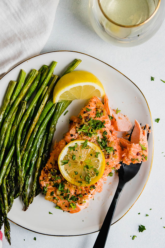 roasted steelhead topped with lemon slice and parsley on a white plate with roasted asparagus