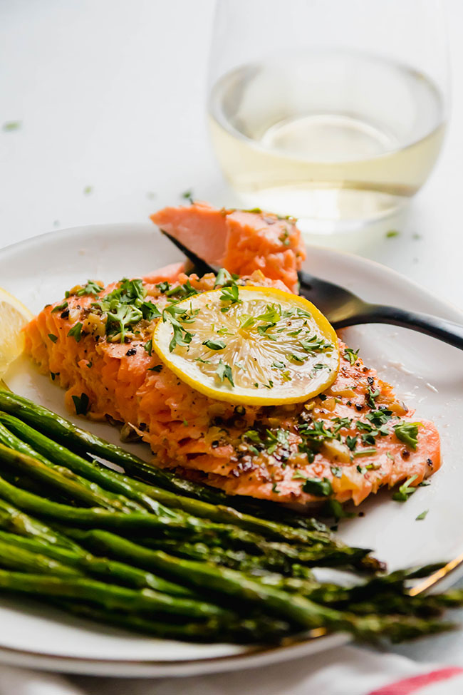 Slice of baked steelhead topped with a lemon slice on a white plate next to roasted asparagus