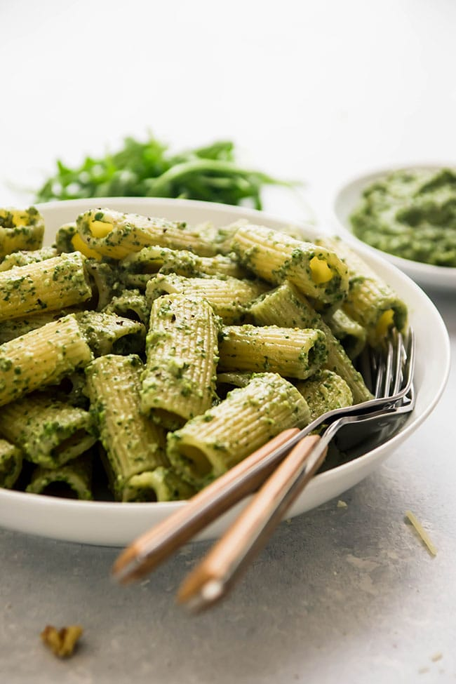rigatoni with pesto in a white bowl with two forks