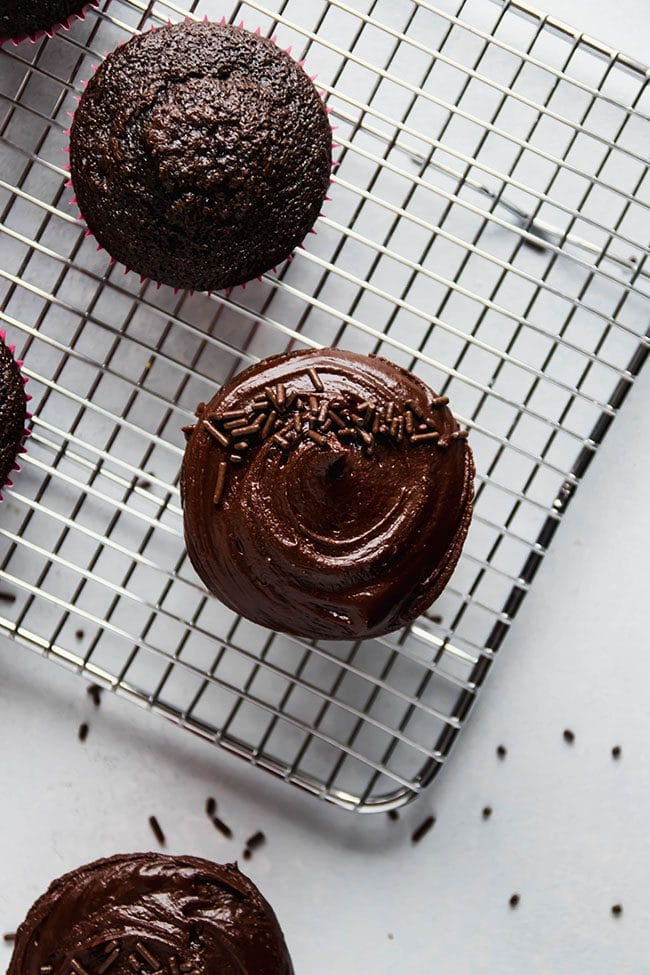 Overhead photo of chocolate cupcakes with chocolate frosting on a cooling rack