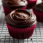 chocolate cupcake with chocolate frosting on a wire cooling rack