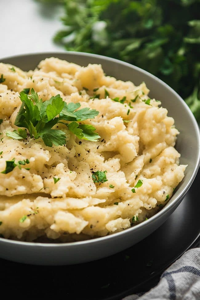 Cauliflower mashed potatoes in a grey bowl topped with fresh parsley