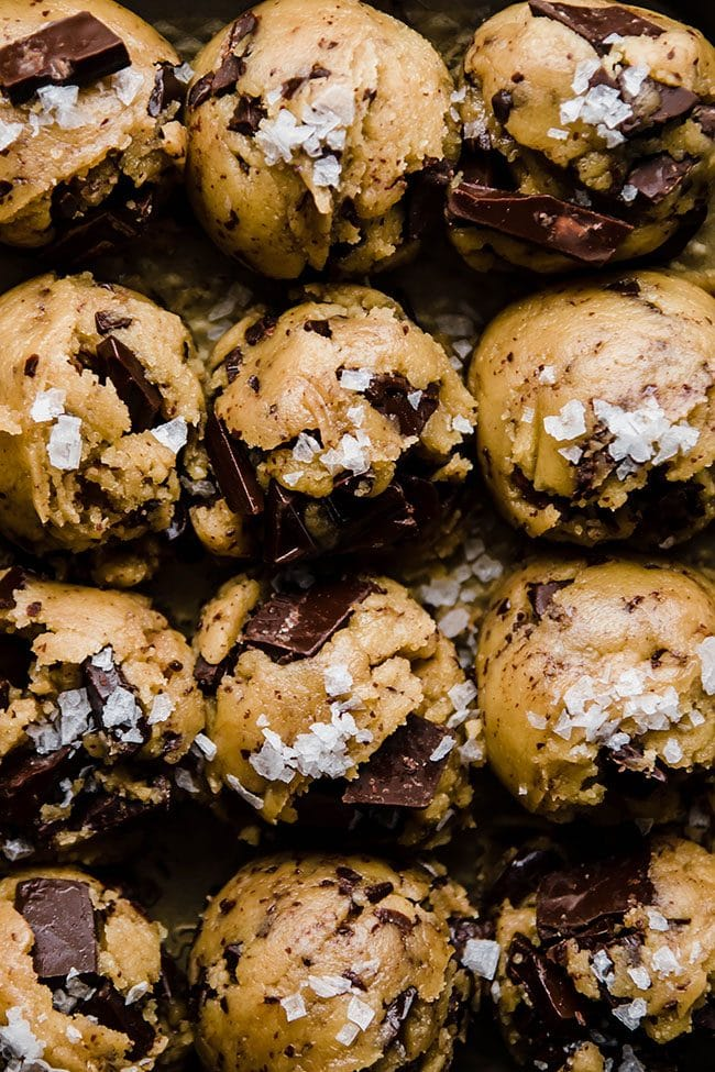 overhead photo of chocolate chip cookie dough balls topped with sea salt
