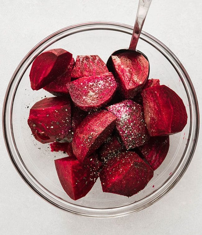 Overhead photo of raw beets in a glass bowl with salt and pepper