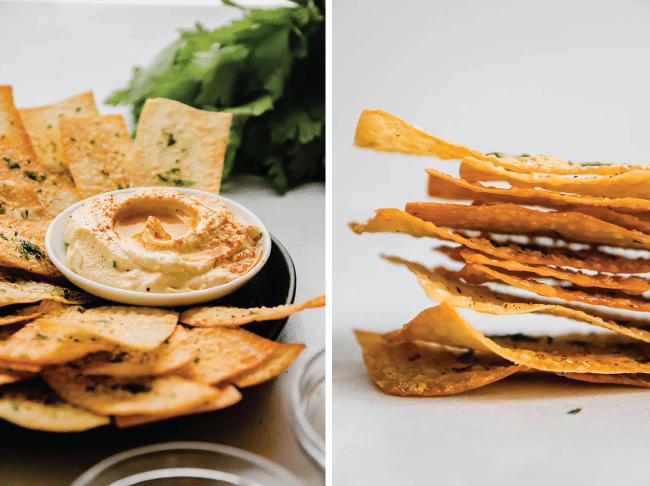 Thin wonton crackers on a black plate next to a bowl of hummus