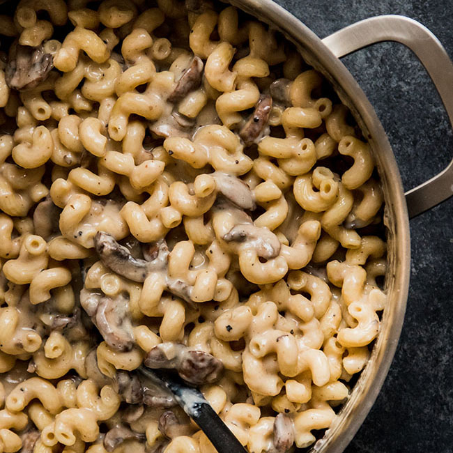Macaroni and cheese with mushrooms in a silver pot on a black background.