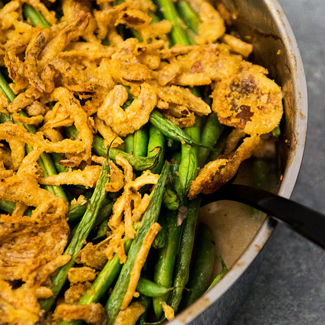Black fork lifting green bean casserole out of a baking dish.
