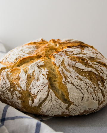 Loaf of crusty bread on a white table next to a blue striped napkin.