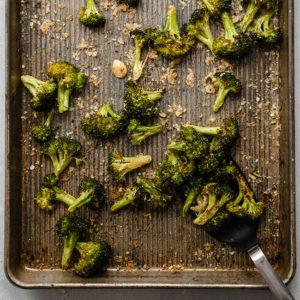 black spatula lifting roasted broccoli from a sheet pan