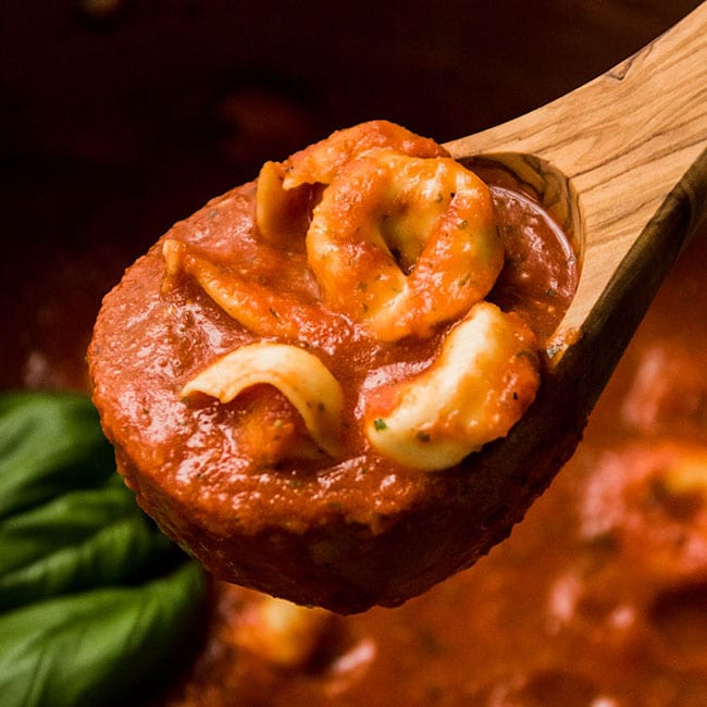 Wooden spoon lifting tortellini tomato soup out of a pot.