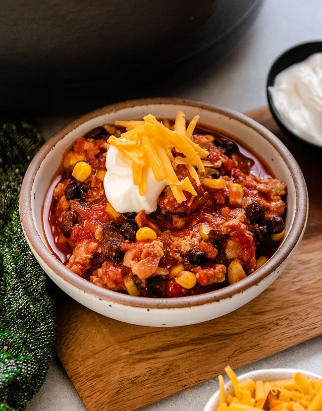 Turkey chili topped with sour cream and shredded cheddar cheese in a white bowl.
