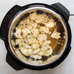 overhead photo of cauliflower florets and vegetable stock in the bowl of an Instant Pot.