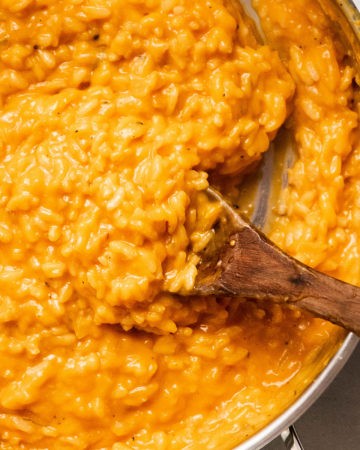 Wooden spoon stirring butternut squash puree into risotto.