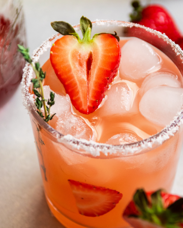Strawberry cocktail garnished with a fresh strawberry, on a white table.