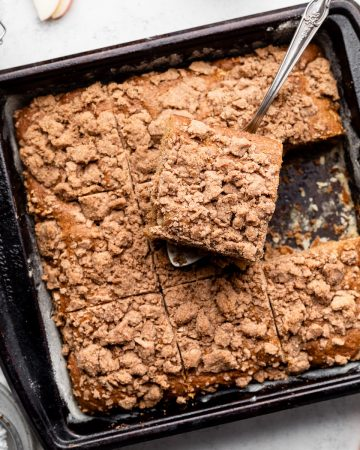 Silver serving spoon lifting a slice of coffee cake out of a square black baking pan.